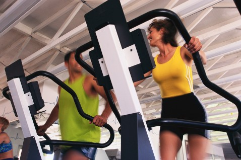 Couple Exercising on Exercise Machines